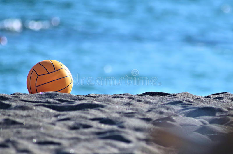 Beach volley ball. A yellow beach volley ball in the sand royalty free stock photos