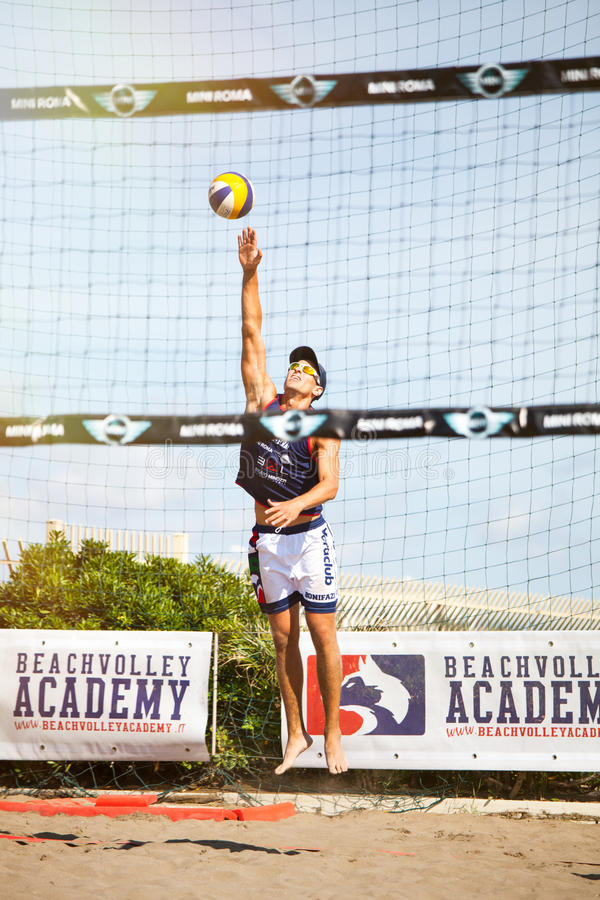 Beach volley. Italian summer league. 30 May 2015. Player of beach volleyball on the sand. The young player is serving the ball. BVA summer league. Rome, Italy royalty free stock image
