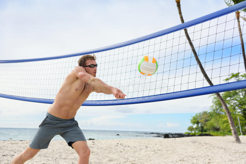 Beach volleyball man playing forearm pass. Hitting volley ball during game on summer beach. Male model living healthy active lifestyle doing sport on beach stock images