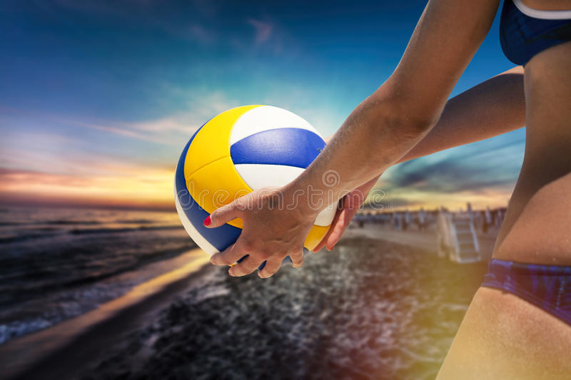 Beach volleyball player, playing summer. Woman with ball. A woman with an athletic body holding a beach volley ball in hand. Sky and colorful sunset on the beach stock images