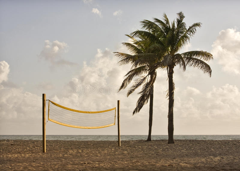 Beach volleyball playing court. With yellow net and palm trees during early morning hours of golden light in Miami Florida with Atlantic Ocean and colorful stock photo