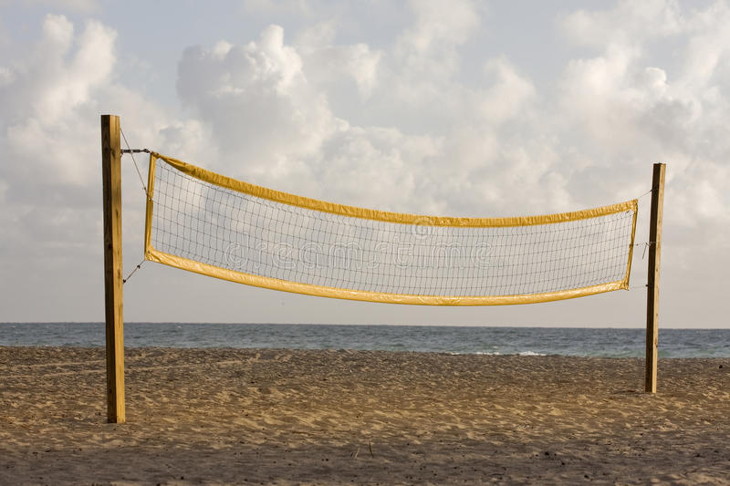Beach volleyball playing court and net. Beach volleyball playing court with yellow net during early morning hours of golden light in Miami Florida with Atlantic royalty free stock photography