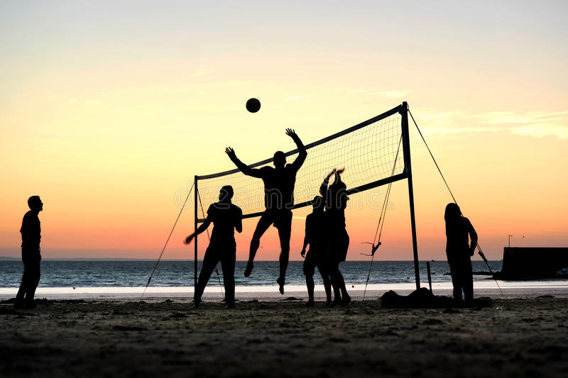 Beach volleyball. Silhouettes of a group of young people playing beach volleyball on the beach in Brittany, France royalty free stock photography