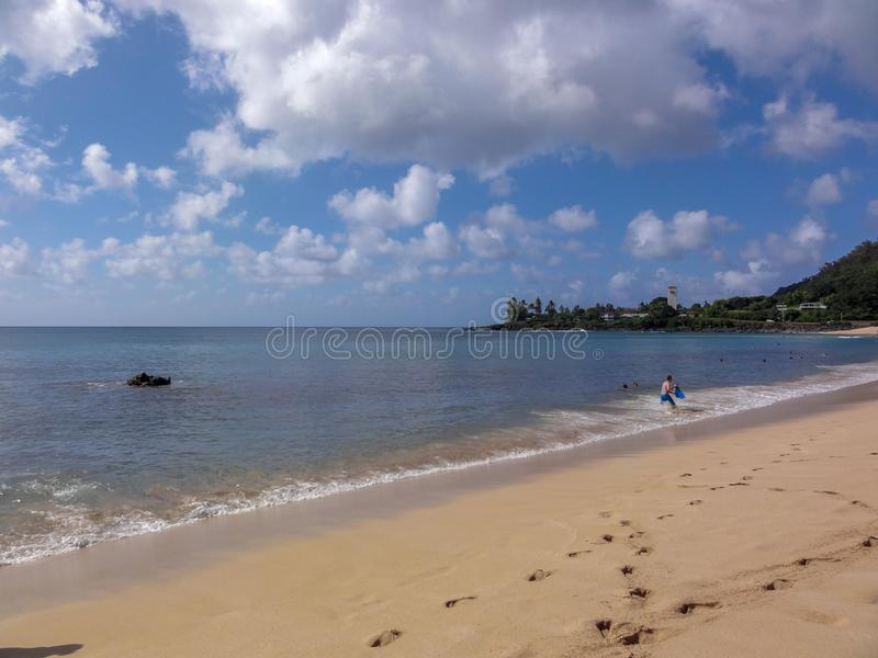 The beach at Waimea Bay. Footprints in the sand and people playing in the water at the beach at Waimea Bay on the island of Oahu in Hawaii stock image