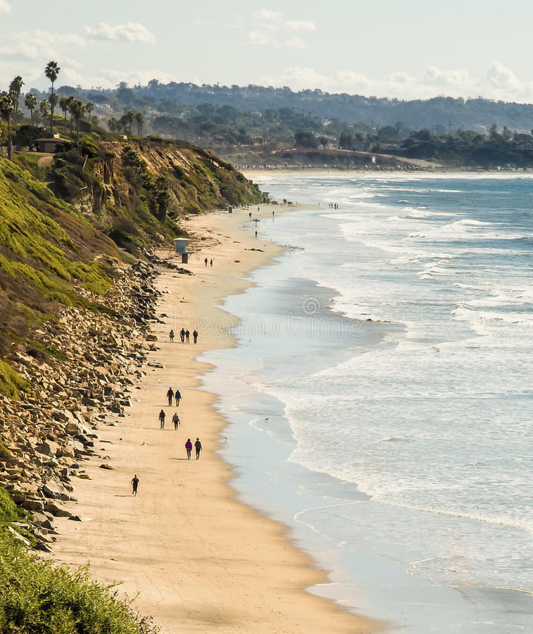 Beach Walking, Encinitas California. People walk along the sandy beach with the surf moving in at high tide, in Encinitas, on the coast of southern California on royalty free stock photography