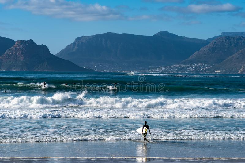 Beach and waves across a bay with beautiful mountains in distance. A view of the beach, breaking waves and mountains across the bay in Kommetjie, Cape Town royalty free stock photo