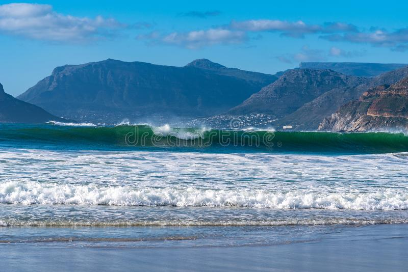 Beach and waves across a bay with beautiful mountains in distance. A view of the beach, breaking waves and mountains across the bay in Kommetjie, Cape Town stock photography