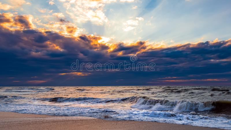 Beach with waves at colorful sunset stock images