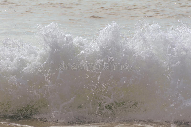 Beach waves crash towards the shore on a hot summer morning royalty free stock images