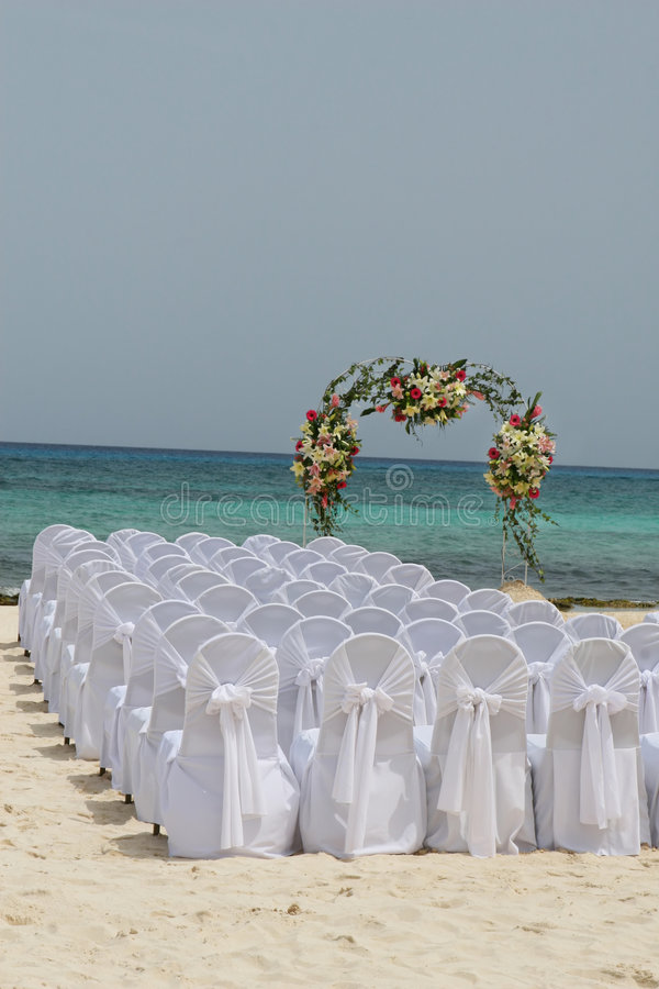 Beach Wedding. White chairs await guests at a beautiful beachside wedding in Mexico stock photo