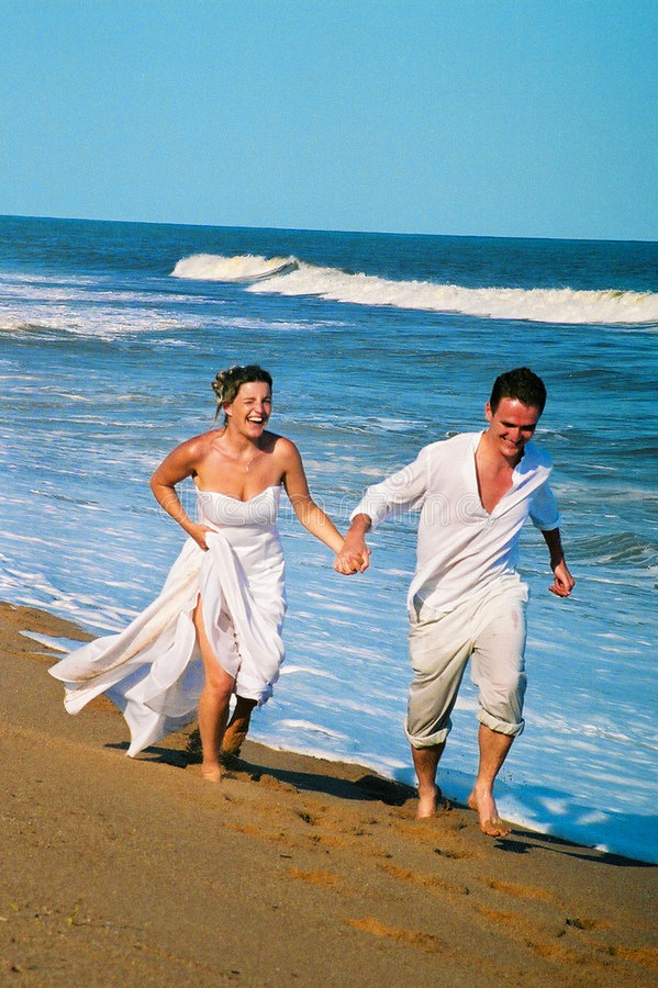 Beach Wedding. A couple on their wedding day, running along the beach royalty free stock image