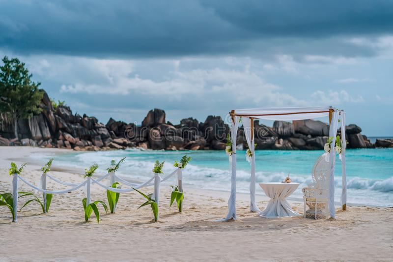 Beach wedding arch ceremonial decorated with white flowers on a tropical white sand beach. Paradise exotic wedding setup. La Digue, Seychelles stock photos