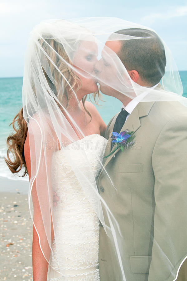 Beach Wedding: Bride and Groom Kiss stock images