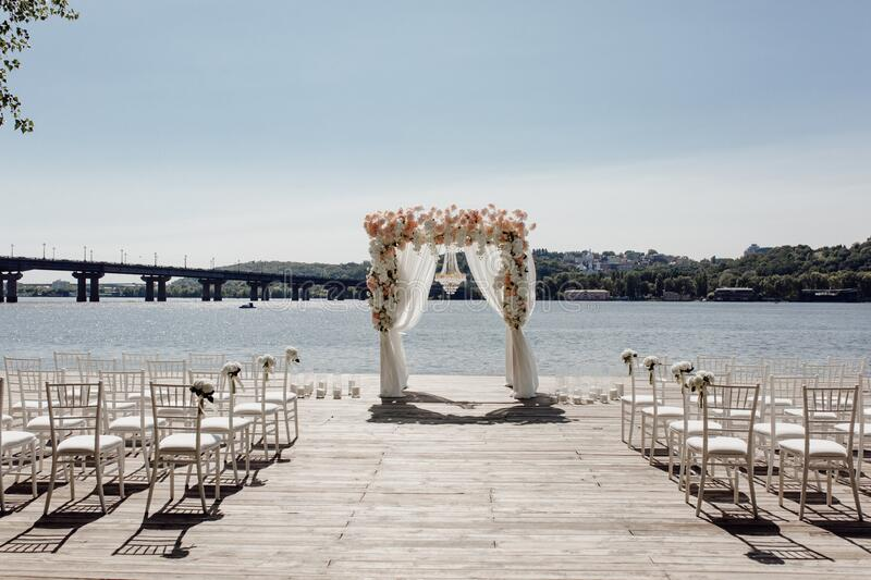 Beach Wedding Day Perfect Place with Arch Altar. Decorated Flowers and Chairs Standing on Wood Flooring and Chairs Ornamented Bouquets. River, Bridge and Forest stock images