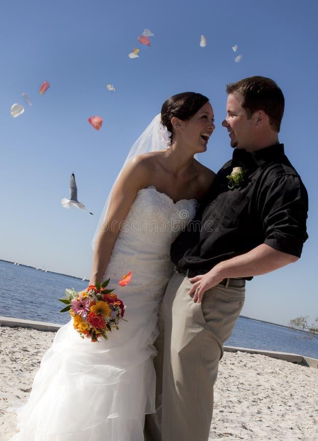 Beach wedding throwing flowers stock photo
