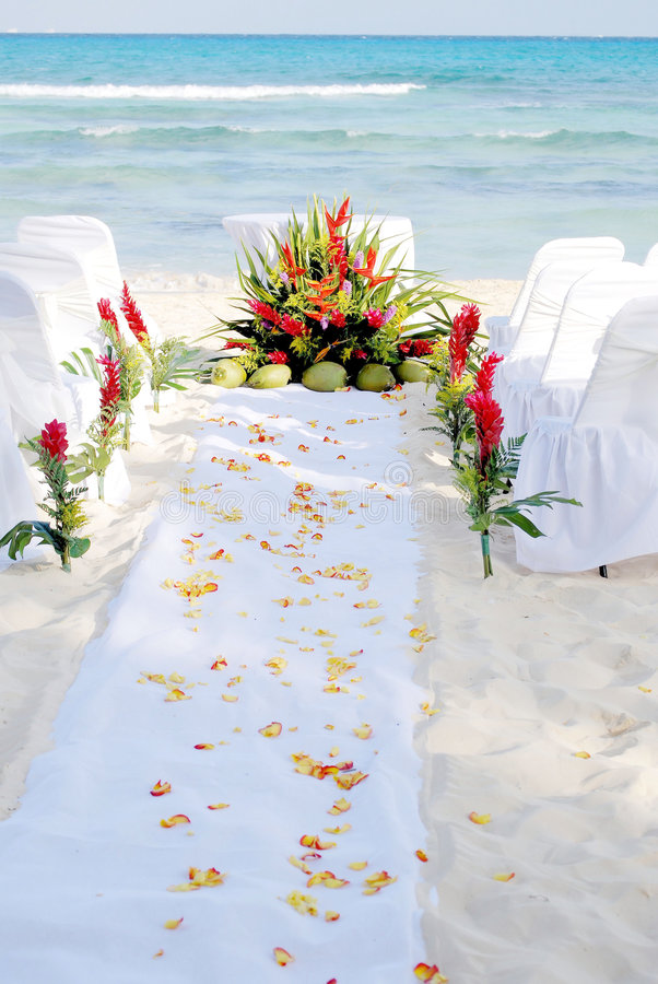 Beach Wedding Walkway. Mexican beach wedding site prepared with floral arrangements, altar, chairs, petal covered aisle stock image