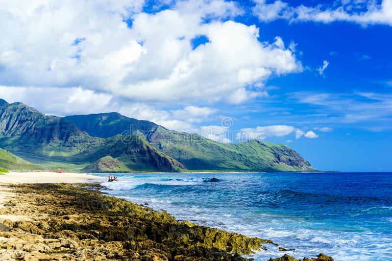 Beach with white sand and blue waves amid lush mountains royalty free stock photography
