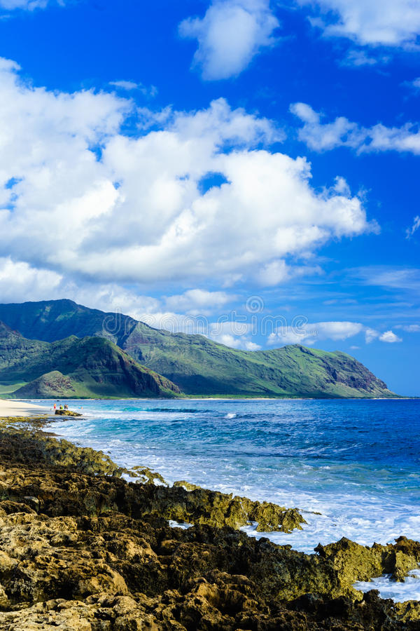 Beach with white sand and blue waves amid lush mountains stock images