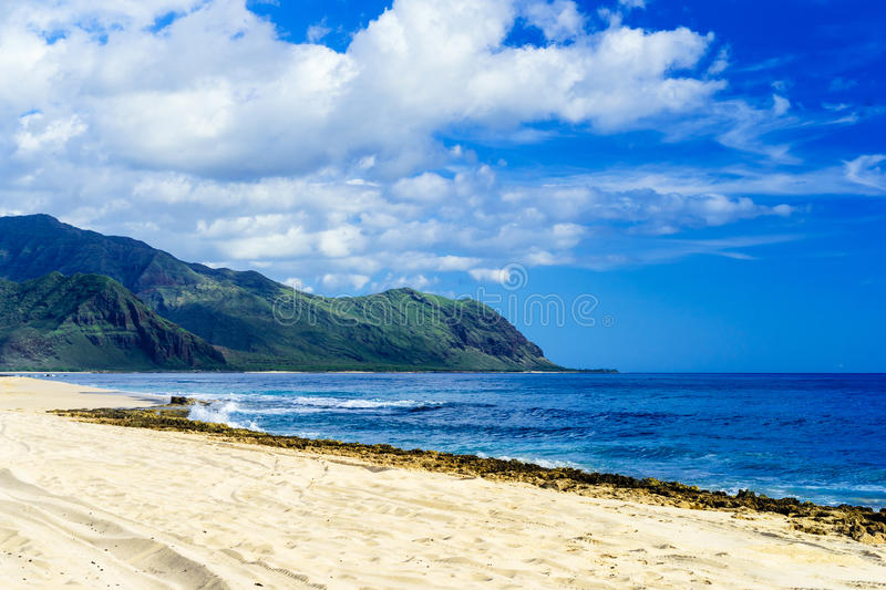 Beach with white sand and blue waves amid lush mountains stock photos