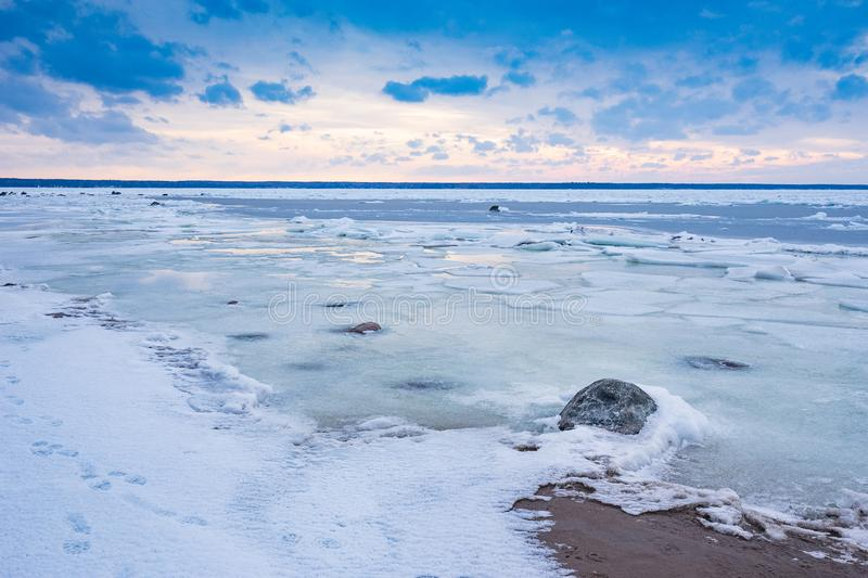 Beach in wintertime. Frozen sea, evening light and icy weather on shore like fairy tale country. Winter on coast. Blue sky, white snow, ice covers the land royalty free stock image