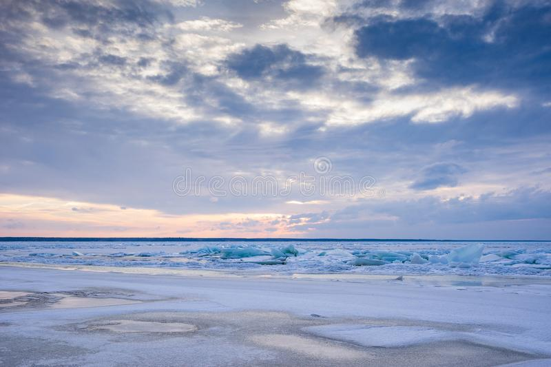 Beach in wintertime. Frozen sea, evening light and icy weather on shore like fairy tale country. Winter on coast. Blue sky, white snow, ice covers the land royalty free stock images