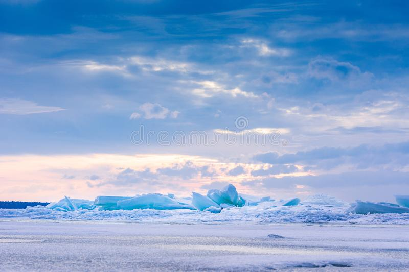Beach in wintertime. Frozen sea, evening light and icy weather on shore like fairy tale country. Winter on coast. Blue sky, white snow, ice covers the land stock photography