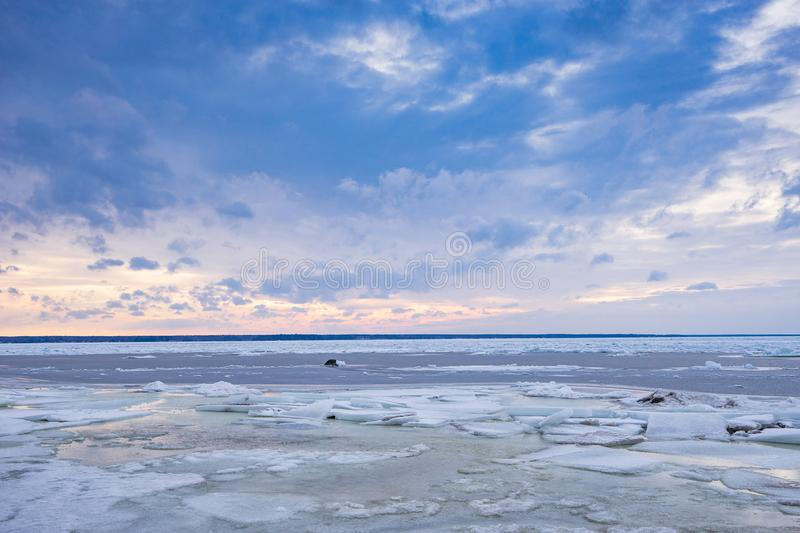 Beach in wintertime. Frozen sea, evening light and icy weather on shore like fairy tale country. Winter on coast. Blue sky, white snow, ice covers the land stock images
