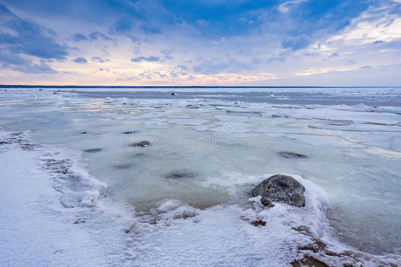 Beach in wintertime. Frozen sea, evening light and icy weather on shore like fairy tale country. Winter on coast. Blue sky, white snow, ice covers the land royalty free stock photography