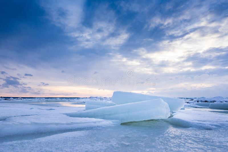 Beach in wintertime. Frozen sea, evening light and icy weather on shore like fairy tale country. Winter on coast. Blue sky, white snow, ice covers the land royalty free stock photos