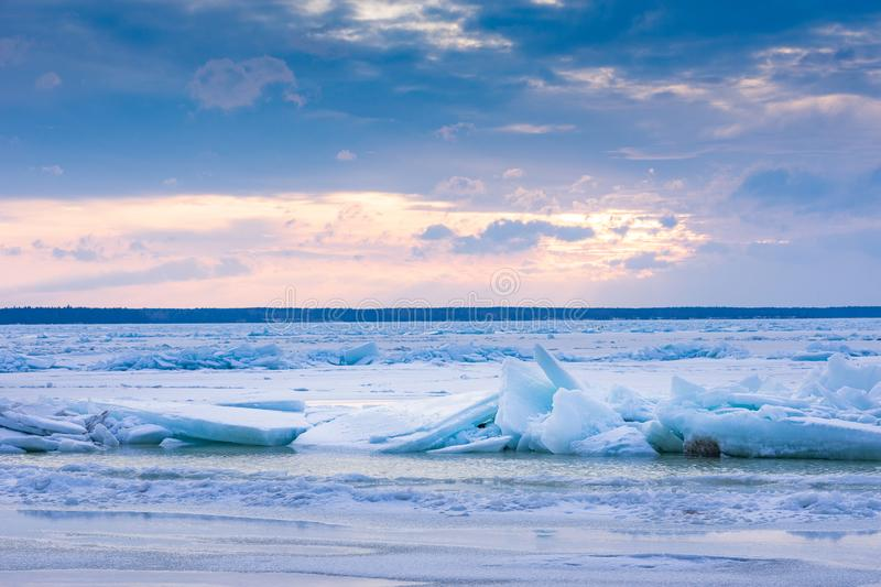 Beach in wintertime. Frozen sea, evening light and icy weather on shore like fairy tale country. Winter on coast. Blue sky, white snow, ice covers the land stock image
