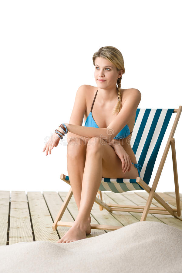Beach - woman in bikini sitting on deck chair. Beach - Young woman in bikini sitting on deck chair relaxing royalty free stock photography