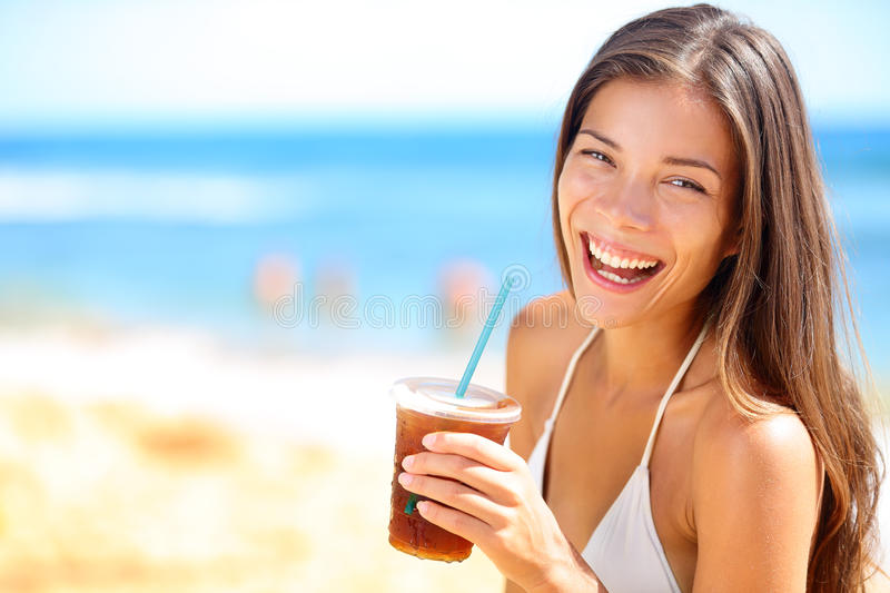 Beach woman drinking cold drink beverage. Having fun at beach party. Female babe in bikini enjoying Ice tea, coke or alcoholic drink smiling happy laughing royalty free stock image