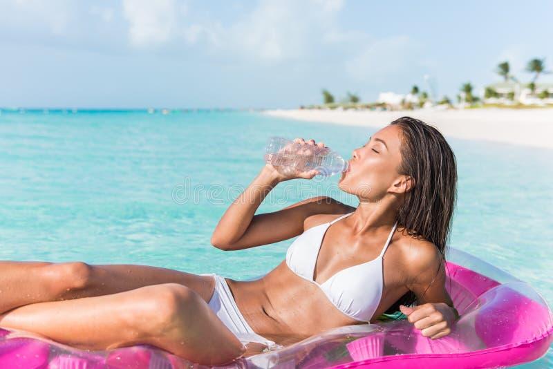 Beach woman drinking water on Caribbean vacation stock photo