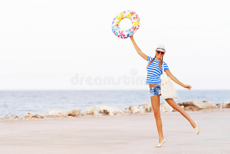 Beach woman happy and colorful wearing sunglasses and beach hat having summer fun during travel holidays stock photo