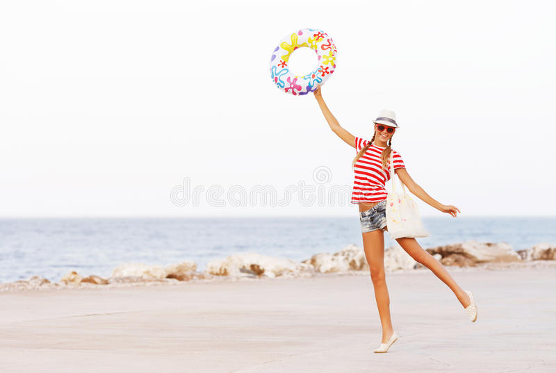 Beach woman happy and colorful wearing sunglasses and beach hat having summer fun during travel holidays vacation stock photography
