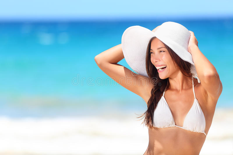 Beach woman happy smiling laughing lifestyle. Bikini girl wearing sun hat looking to side at copy space excited at joyful. Beautiful mixed race woman having royalty free stock photos