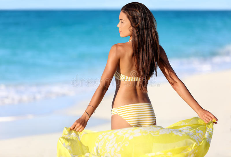 Beach woman relaxing in bikini and cover-up. Beach woman relaxing in yellow bikini and cover-up pareo beachwear enjoying sunset. Beautiful Asian girl model from stock photos