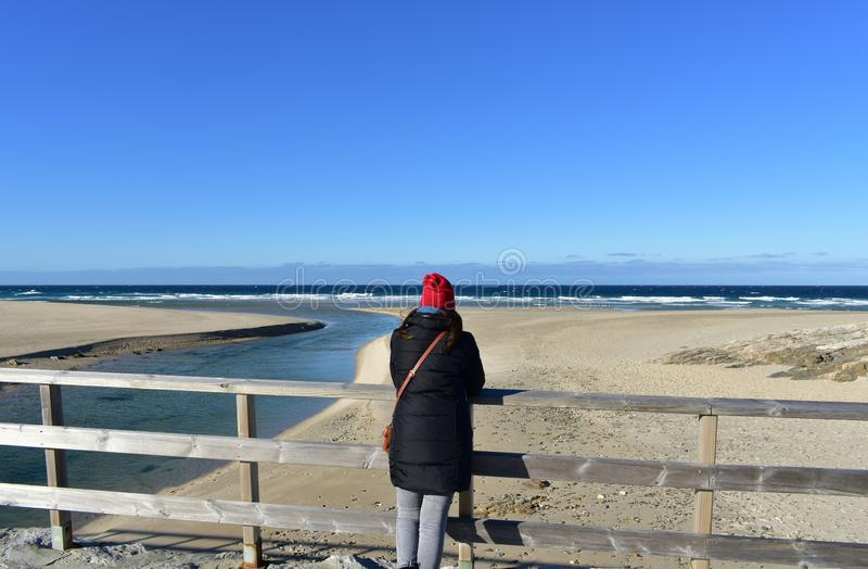 Beach with woman resting on a wooden handrail and looking at the view. Winter clothes and red hat. Sunny day, blue sea with waves royalty free stock images