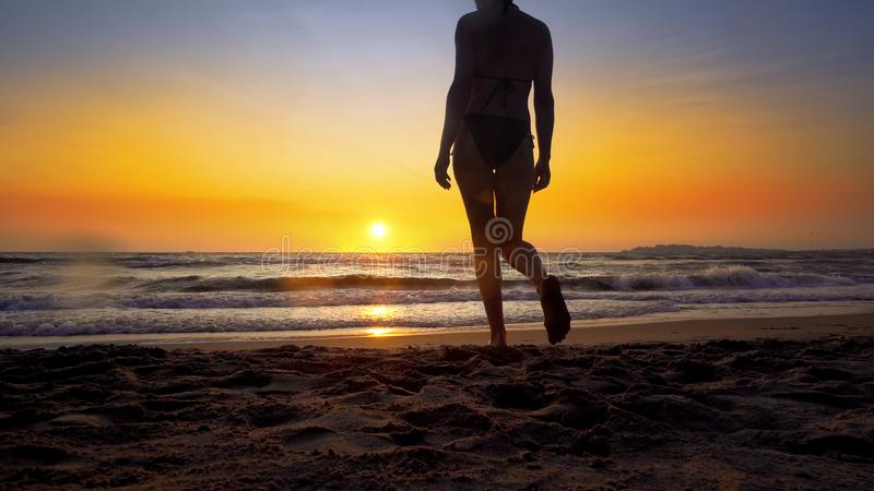 Beach woman running out of water at sunset enjoying freedom during summer holidays vacation travel royalty free stock photo
