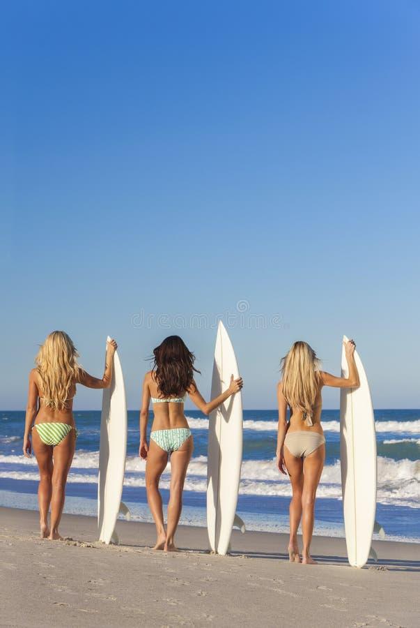 Beach Women Surfer Girls In Bikinis & Surfboards royalty free stock image