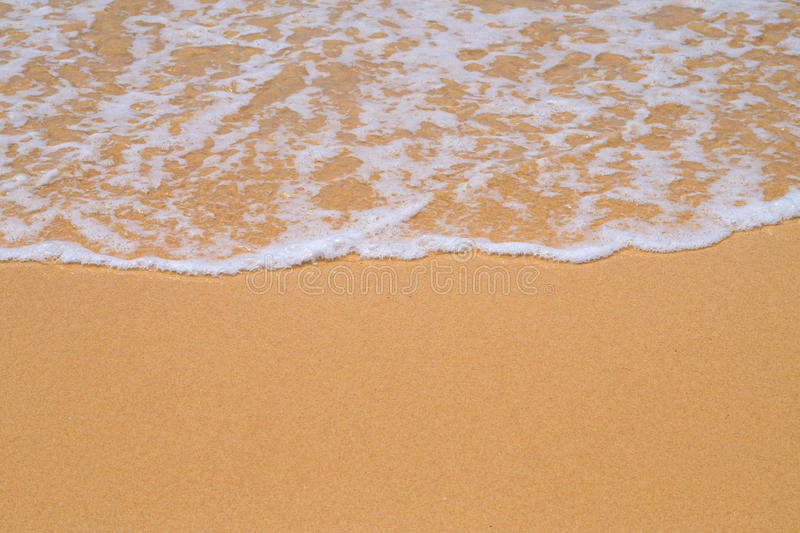 Beach yellow sand covered with wave white foam stock photography