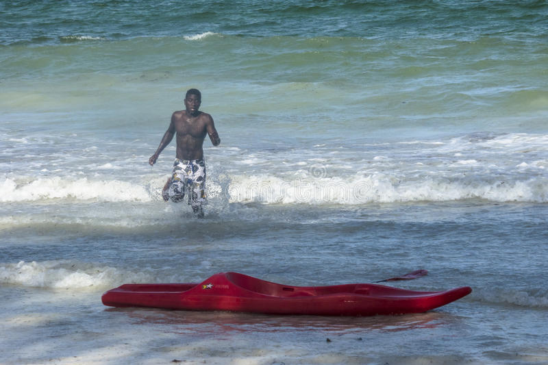 Beach in Zanzibar. The man learns to swim in a red kayak in the Indian Ocean on the beach in Kiwengwa Village, Zanzibar, Tanzania, Africa stock image