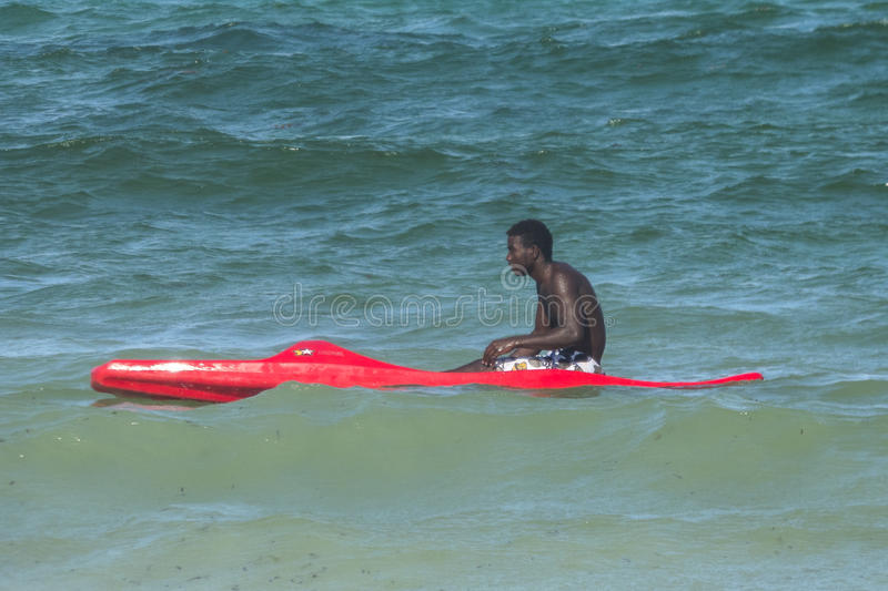 Beach in Zanzibar. The man learns to swim in a red kayak in the Indian Ocean on the beach in Kiwengwa Village, Zanzibar, Tanzania, Africa royalty free stock images