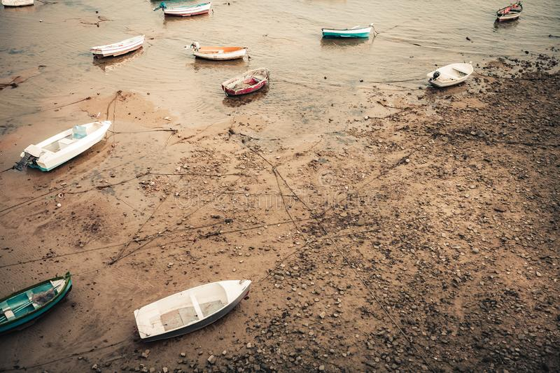 Beached fishing boats in a bay. Rowboat during low tide in a sand and pebble beach shore. Playa de la Caleta Beach, Cadiz, Spain royalty free stock image