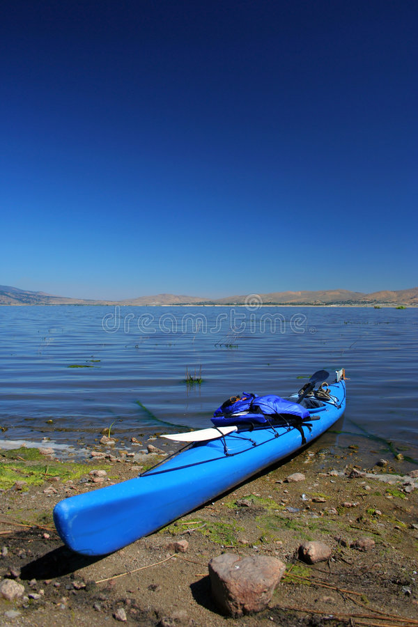 Beached Kayak. A beached kayak on the shoreline of a small lake in northern Nevada. Paddles and life vest eviden in photo stock image