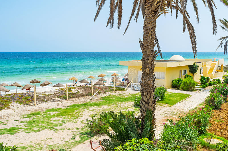 The beaches of Tunisia. The cozy beach with straw sunshades neighbors with the scenic green garden with palms and blooming bushes, El Kantaoui resort, Tunisia stock image