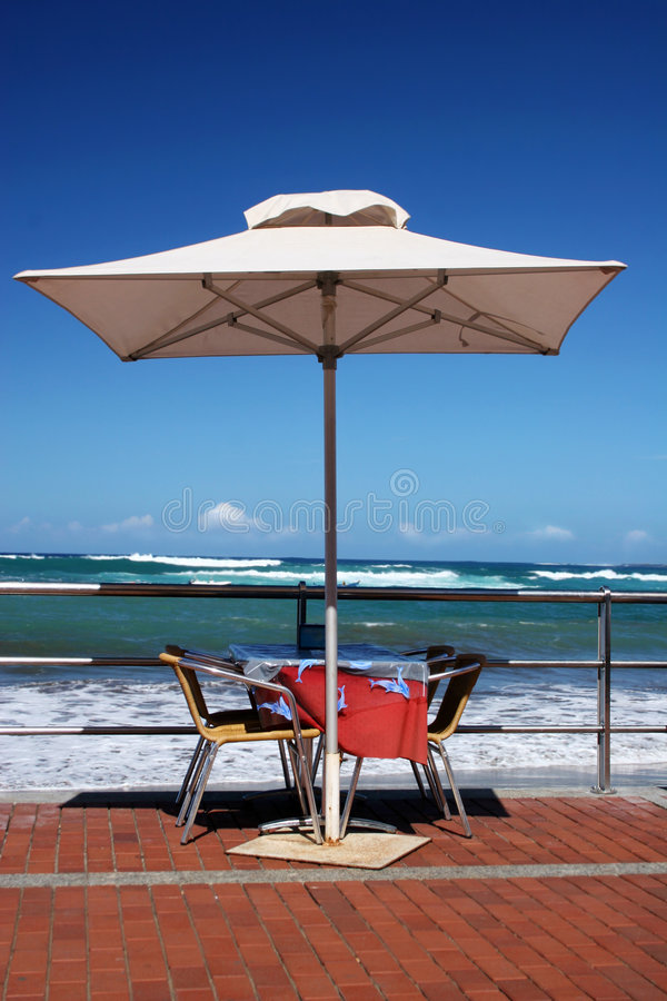 Beachfront Table. With white umbrella and blue sky stock photo
