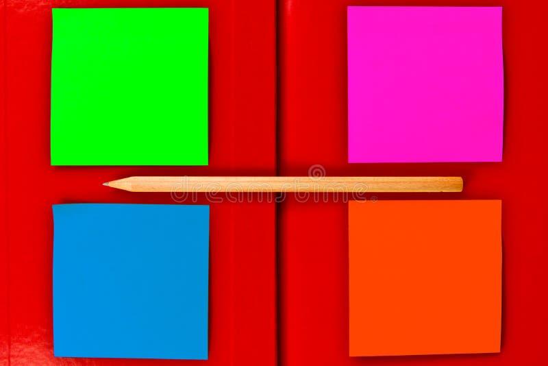 Beachten Sie über rotes Notizbuch lizenzfreie stockfotografie