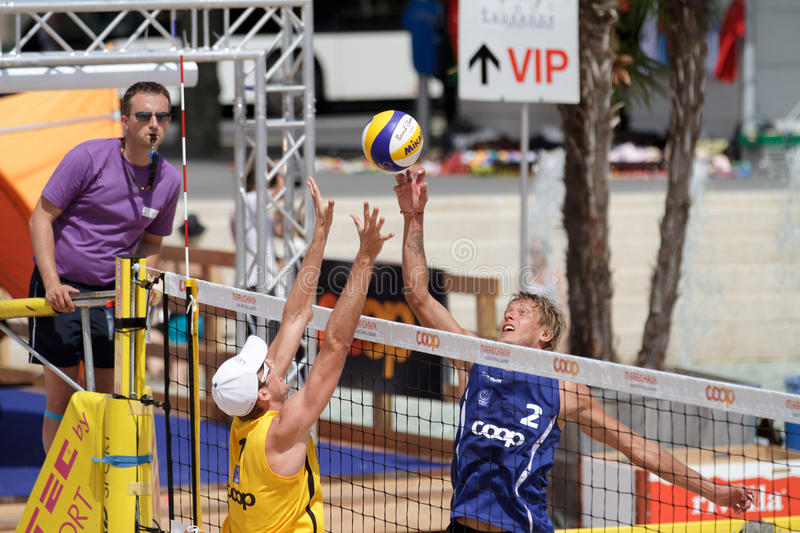 BeachVolley - Lausanne Satellite CEV 2012. Rivo Vesik of Estonia pokes a ball above the block of Anders Lund Hoyer, under the watchful eye of the referee. Shot stock image