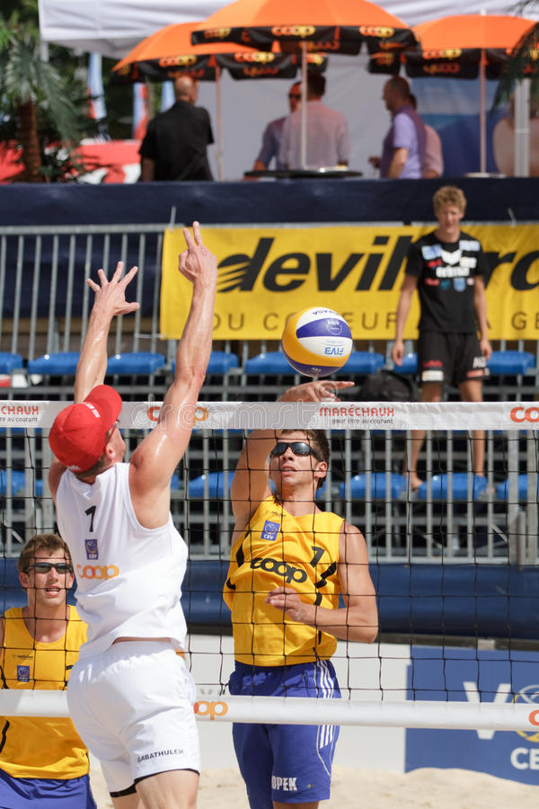 BeachVolley - Lausanne Satellite CEV 2012. Dawid Popek of Poland spikes a ball past Switzerland's Philip Gabathuler's block under the eyes of his teammate royalty free stock images